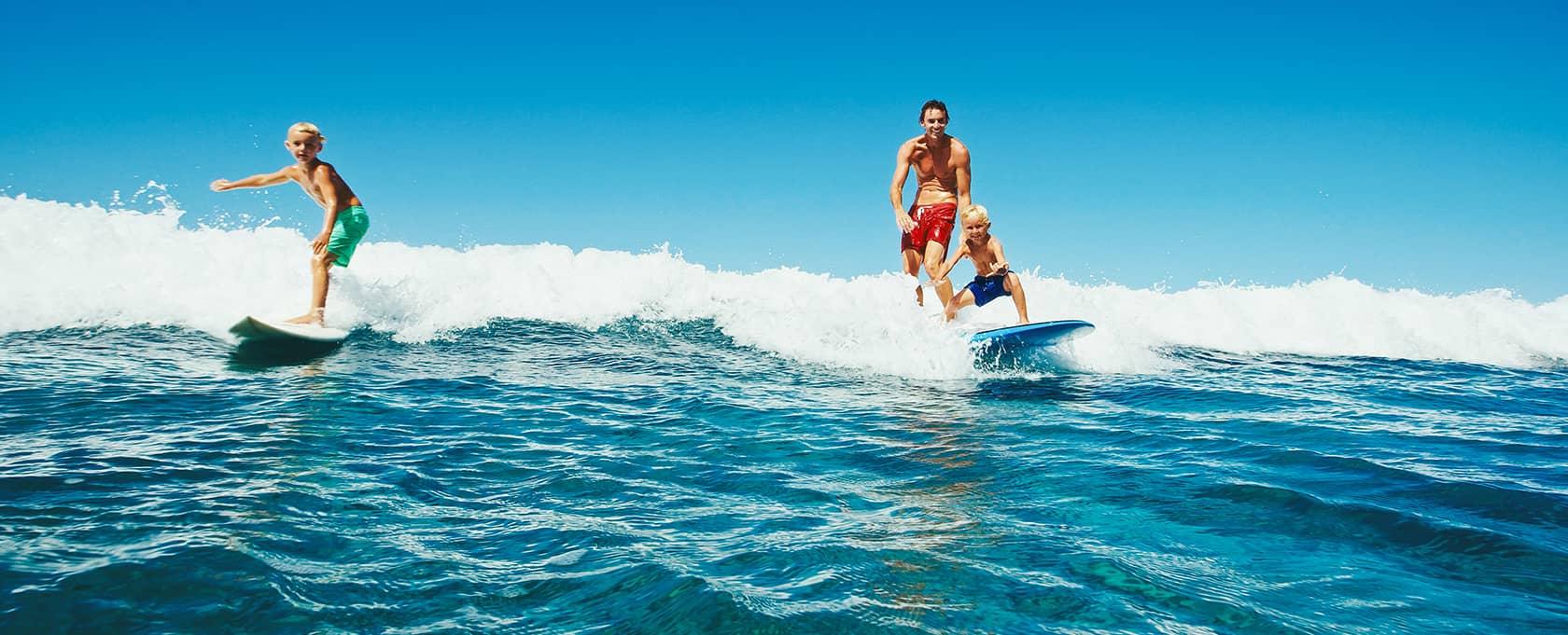 Une famille surfe sur l'océan atlantique dans les Landes