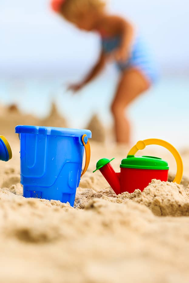 une petite fille joue dans le sable en construisant un château