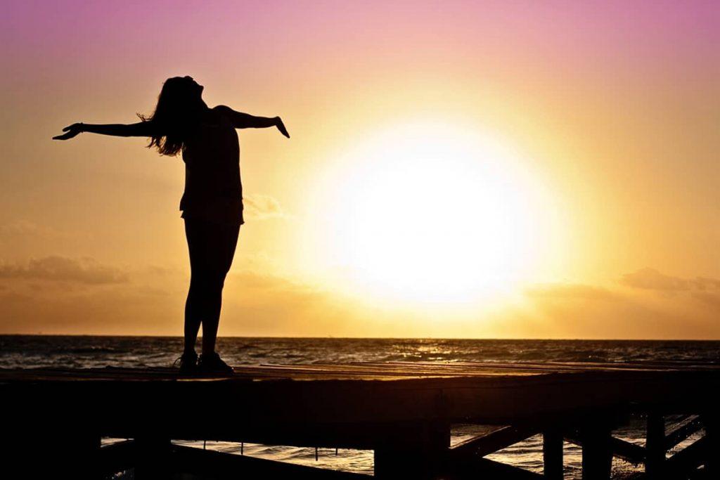 Une femme prend l'air sur un ponton au coucher de soleil